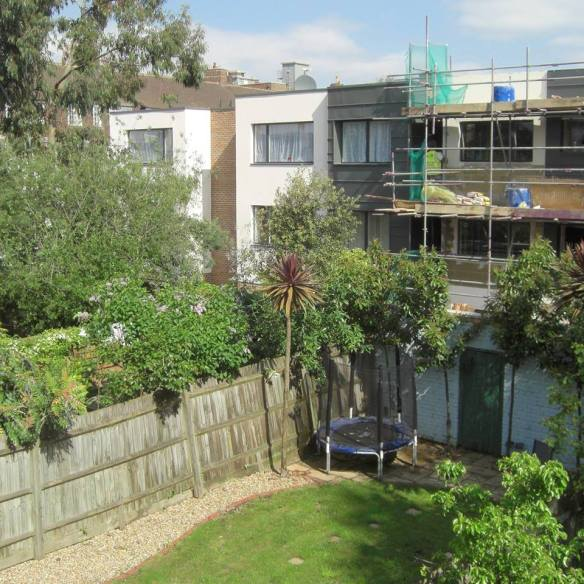 Buildings erected on immediate back garden walls belonging to a small Streatham Hill